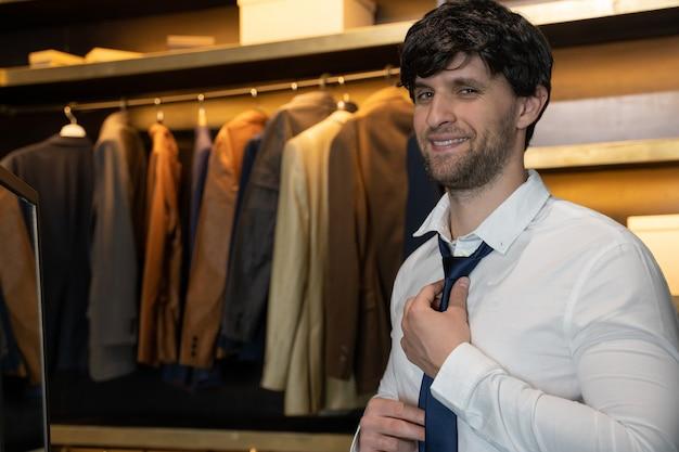 シャツを着た男性が服を着て、楽屋で首の周りの青いネクタイを調整します