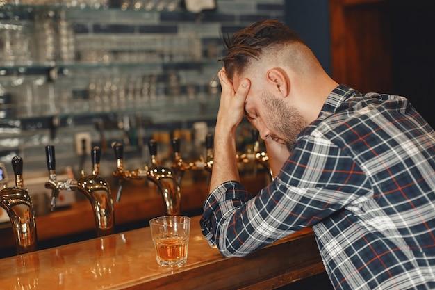 셔츠에 남자는 그의 손에 유리를 보유하고 있습니다. 남자는 술집에 앉아서 머리를 잡고 있습니다.