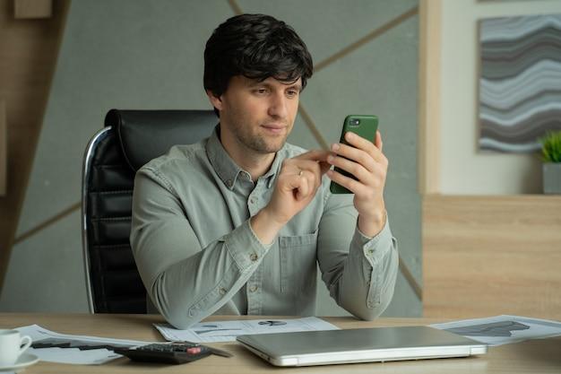 Человек в рубашке сидит в офисе и использует смартфон для работы
