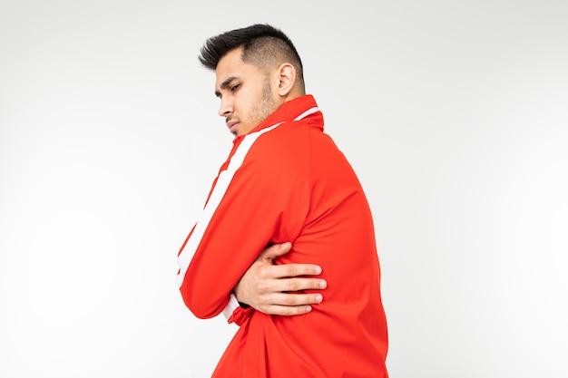 Мужчина в спортивном красном костюме обнимает себя, чтобы согреться