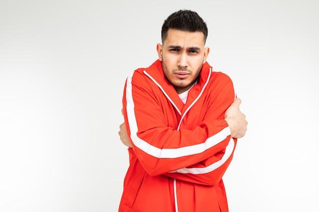 Мужчина в спортивном красном костюме съеживается от холода, обнимая себя на белом фоне с копией пространства.
