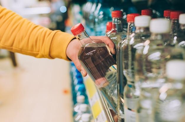 店の男は、ラックを背景に飲料水のボトルを手に持っています。