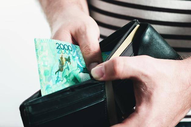 Мужчина в полосатой футболке держит черный кожаный бумажник с казахстанскими банкнотами.