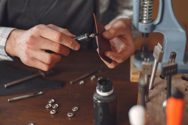 Человек в студии создает изделия из кожи