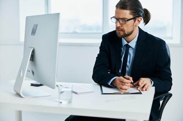スーツを着た男がコンピューター技術で働いている役人
