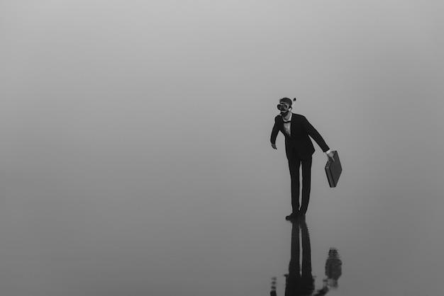 물 위에 서있는 그의 손에 서류 가방이있는 다이빙 튜브가있는 양복과 마스크의 남자