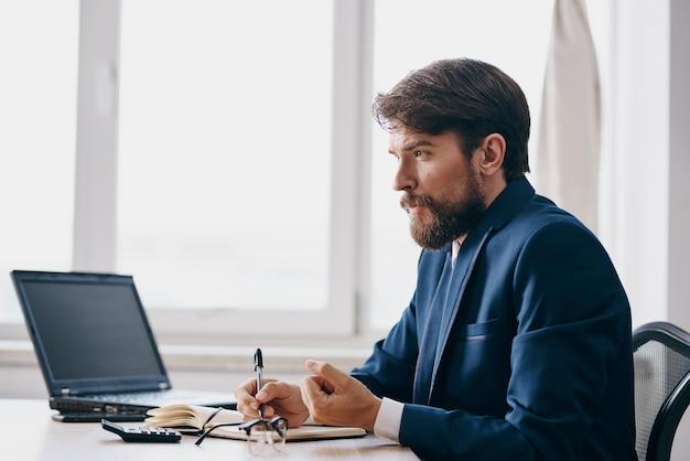 노트북 통신 관리자 앞 테이블에 정장을 입은 남자