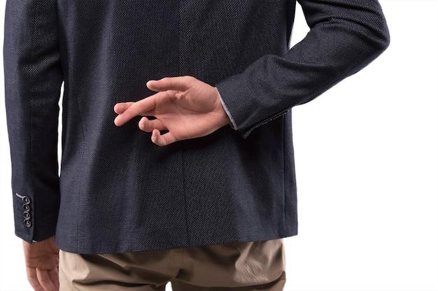 Мужчина в костюме скрестил пальцы за спиной