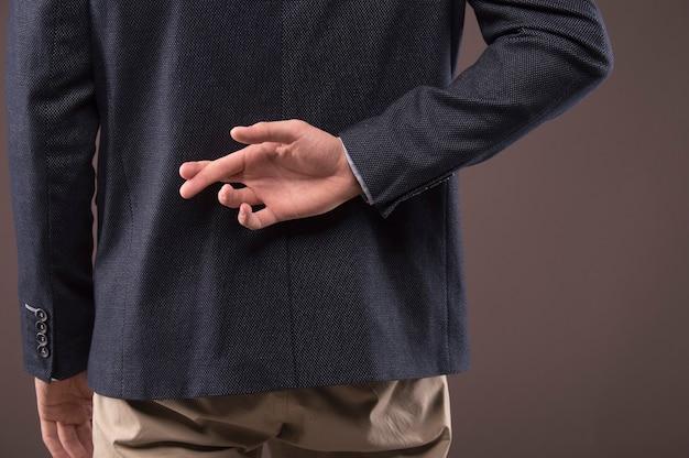 양복을 입은 남자가 등 뒤에서 손가락을 교차