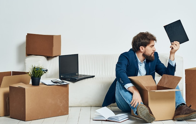 スーツの感情の男は床にボックスを移動して動作します