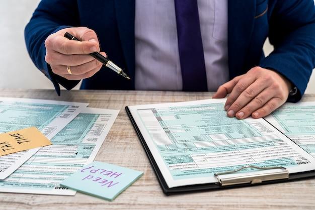 양복을 입은 남자가 미국 개인 1040 세금 양식을 작성합니다. 세금 시간. 회계 개념