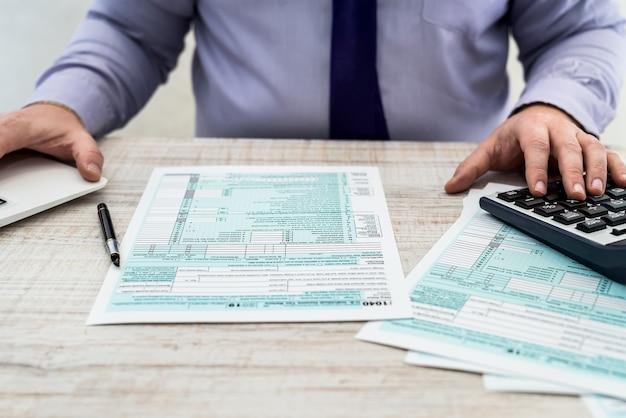 スーツを着た男性が米国の個人1040税務フォームに記入します。課税時間。会計の概念
