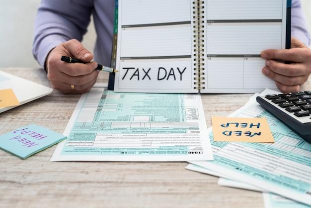 スーツを着た男性が米国の個人1040税務フォームに記入します。課税時間。会計の概念 Premium写真