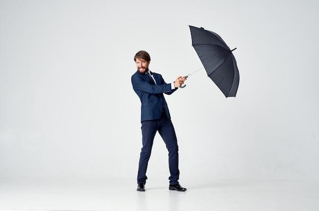 彼の頭の雨よけの専門家の上に傘を持っているスーツを着た男