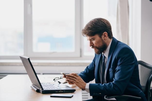 ノートパソコンのエグゼクティブの成功の前にオフィスでスーツを着た男