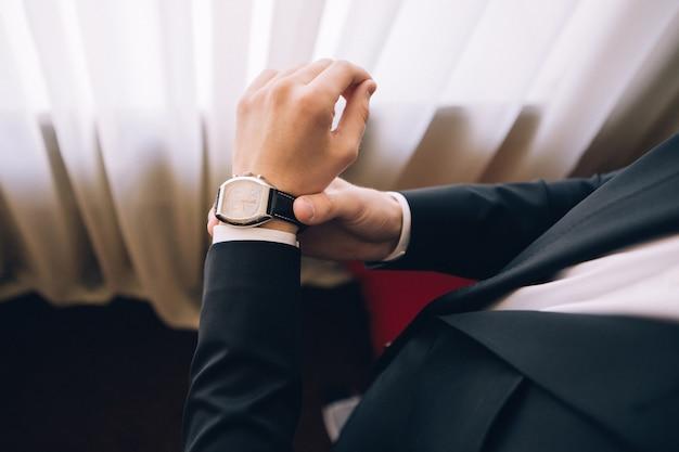 양복 입은 남자는 시계를 입고있다. 검은 양복을 입은 남자. 남자는 시간을 본다. 비즈니스 정장에 남자가있다입니다. 젊은 남자는 손목 시계를 착용합니다.
