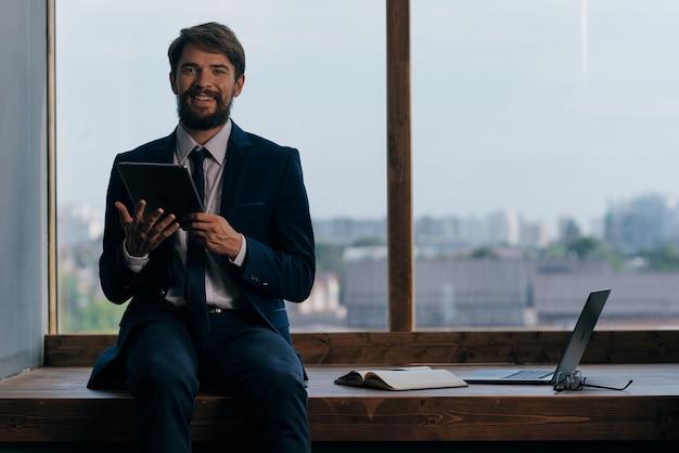 ノートパソコンの通信で窓の近くのスーツを着た男