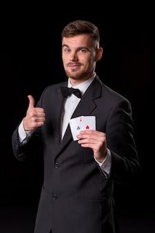 黒の背景にギャンブルのカードでポーズをとってスーツを着た男