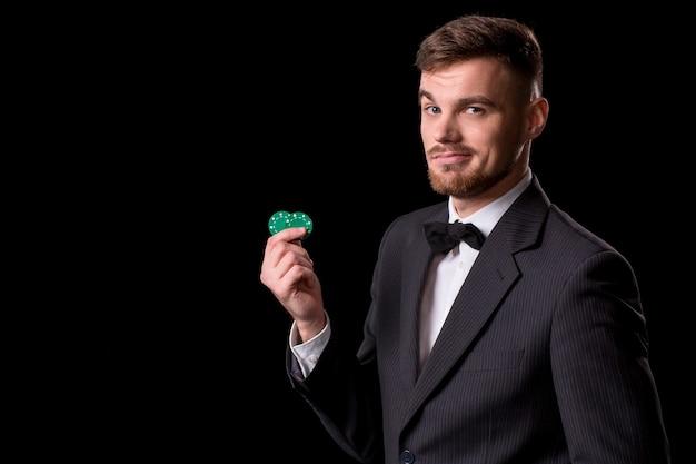 黒の背景にギャンブルのためのチップでポーズをとってスーツの男