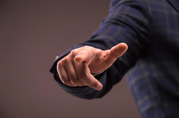 Мужчина в костюме нажимает пальцем на дисплей