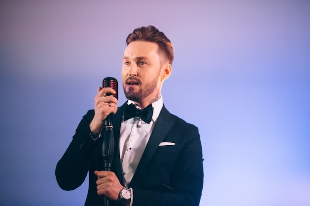 ステージで歌うスーツを着た男