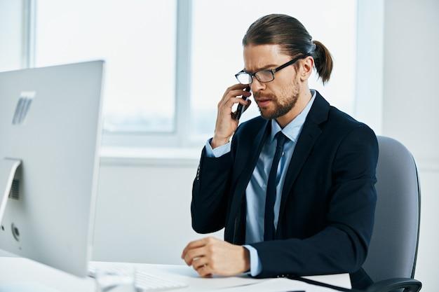 コンピューターチーフの前の机に座っているスーツを着た男