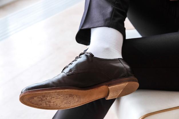 Человек в костюме сидит со скрещенными ногами