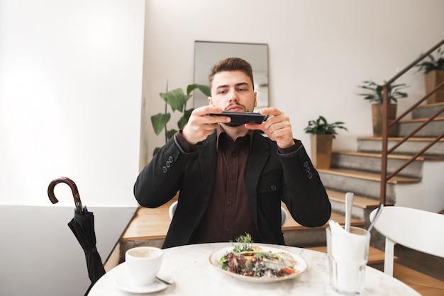 Мужчина в костюме сидит в светлом уютном ресторане и фотографирует еду на смартфоне.