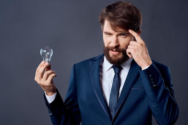 성공 감정에 대한 그의 손에 램프가 있는 양복을 입은 남자