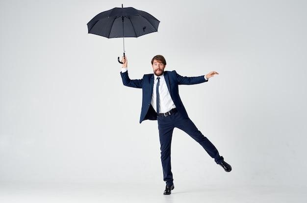 手に傘を持ったスーツを着た男が雨から身を守るエレガントなスタイルのフルレングス。高品質の写真