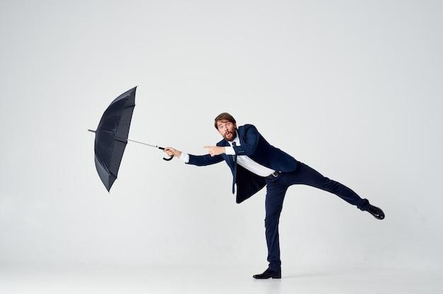 手に傘を持ったスーツを着た男が雨から身を守るエレガントなスタイルのフルレングス