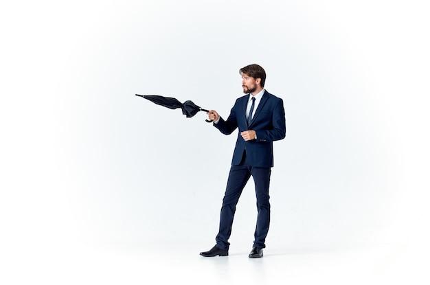 Человек в костюме с зонтиком в руках защиты от непогоды