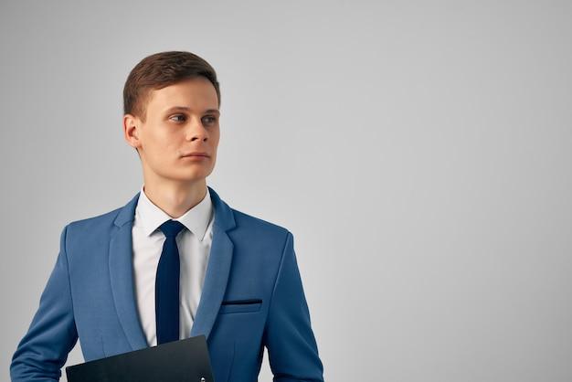 彼の手にドキュメントを持つスーツの男プロのオフィスの明るい背景