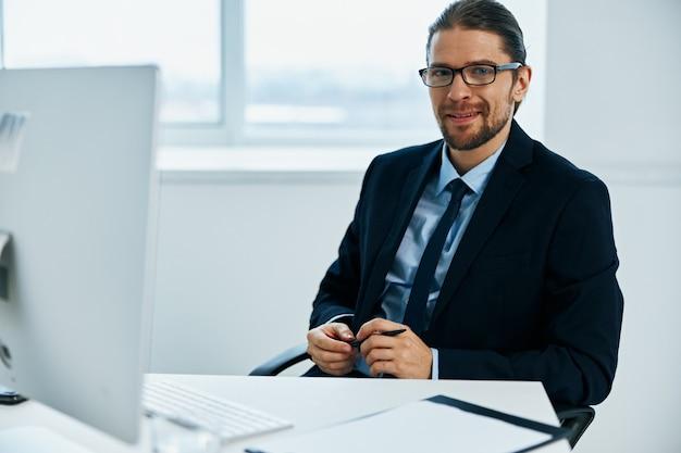 コンピューター文書の幹部の前で働くスーツを着た男