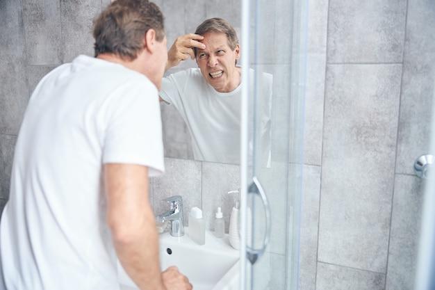 벽에 거울 앞에서 피부 검사를 수행하는 티셔츠를 입은 남자 프리미엄 사진
