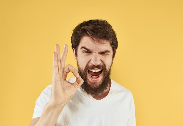 彼の手でtシャツの前向きなジェスチャーで男白いtシャツのふさふさしたあごひげ