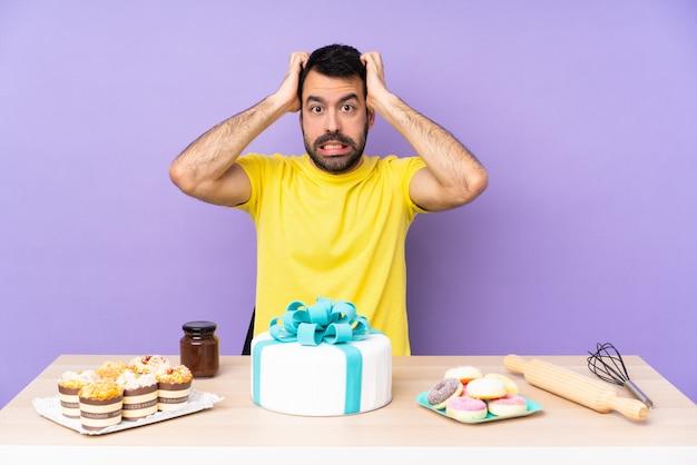 大きなケーキを持つテーブルで男はイライラし、頭に手をとる