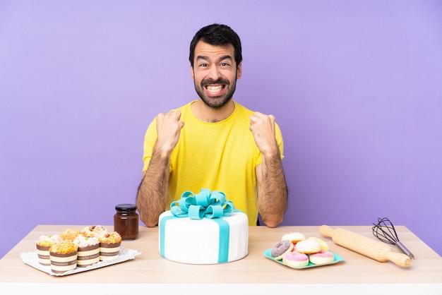 悪い状況に欲求不満の大きなケーキを持つテーブルの男