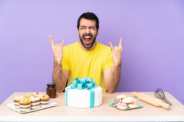 岩のジェスチャーを作る大きなケーキを持つテーブルの男
