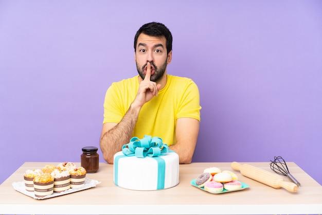 입에 손가락을 넣어 침묵 제스처의 표시를 보여주는 큰 케이크와 함께 테이블에 남자