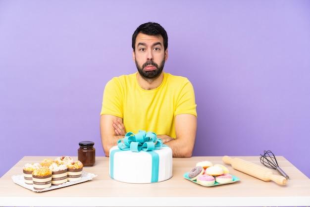 悲しくて落ち込んだ表情の大きなケーキを持つテーブルの男