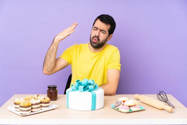 疲れて病気の表情で大きなケーキとテーブルの男