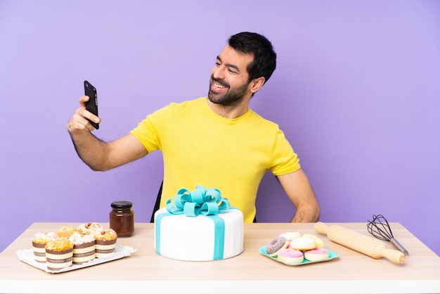 孤立した紫の壁に大きなケーキを持つテーブルの男