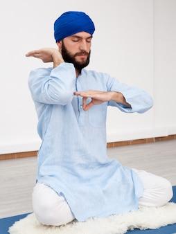 Человек в тюрбане сидит на коврике, занимаясь йогой мудрой