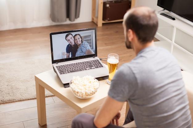 検疫中に友人とビデオ通話をしている男性。
