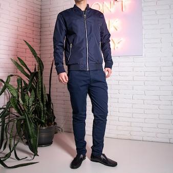 Мужчина в теплой синей осенней куртке у кирпичной стены.