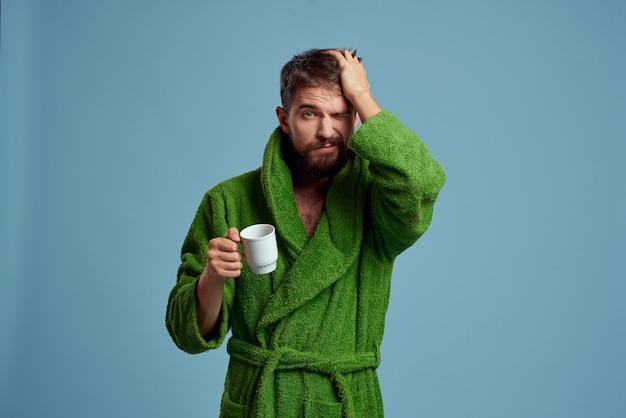 Мужчина в теплом халате с чашкой горячего напитка