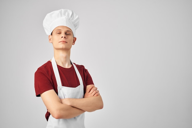 制服のキッチンで働く頭に帽子をかぶった白いエプロンの男