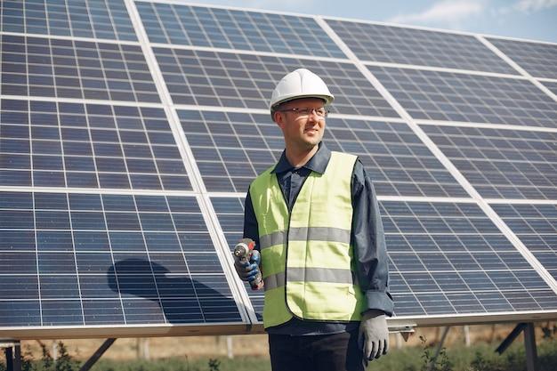 Человек в белом шлеме возле солнечной панели