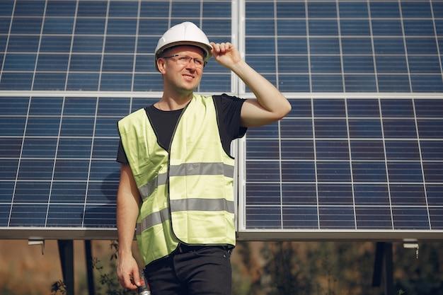 태양 전지 패널 근처 흰색 헬멧에 남자